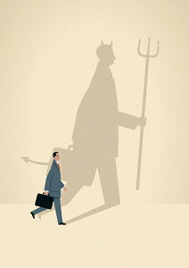 Businessman with large devil shadow