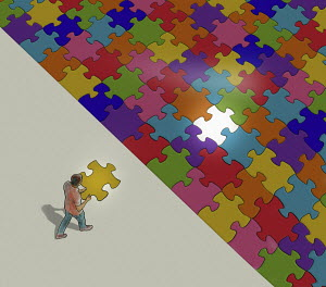 Man with last piece of jigsaw