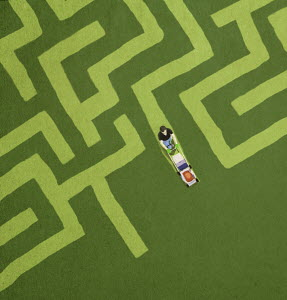 Man mowing maze shape in lawn