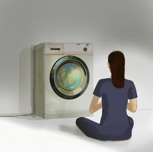 Woman meditating in front of washing machine