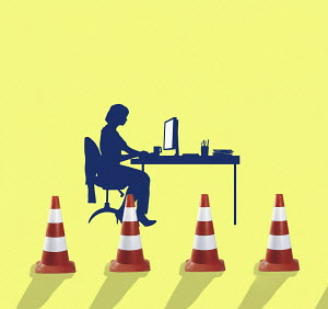 Businesswoman working at desk behind traffic cones