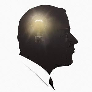 Businessman with light bulb glowing inside head