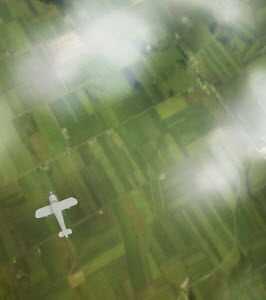 Overhead view of plane flying over green landscape