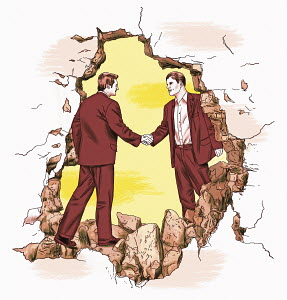 Businessmen shaking hands through hole in wall