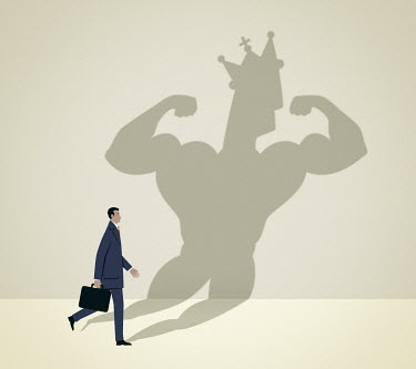 Businessman walking casting muscular shadow wearing crown
