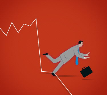Businessman tripping up over falling line graph