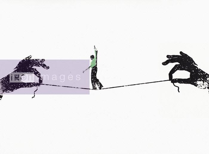 Businessman walking tightrope on string between two hands - Businessman walking tightrope on string between two hands - Katie Edwards