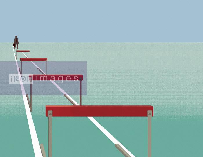 Businessman facing row of hurdles - Businessman facing row of hurdles - Andrew Baker