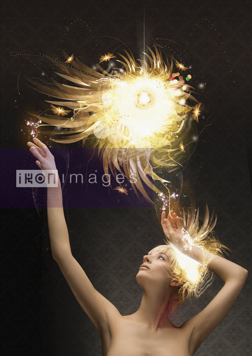 Woman reaching up to abstract glowing ball - Woman reaching up to abstract glowing ball - Aeriform & Maria Teijeiro