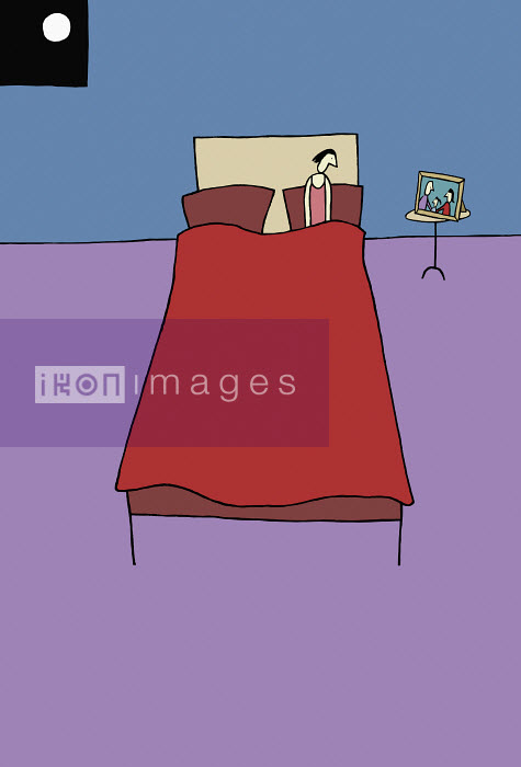 Lonely woman in bed looking at family photograph on nightstand - Lonely woman in bed looking at family photograph on nightstand - Justine Beckett