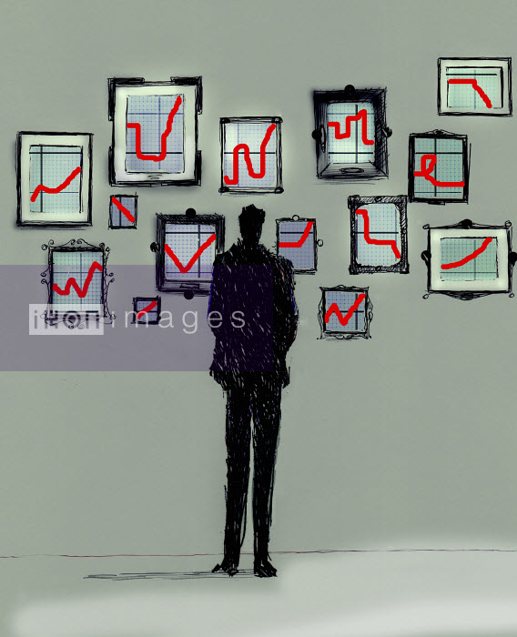 Businessman looking at gallery of different line graph charts on wall Gary Waters
