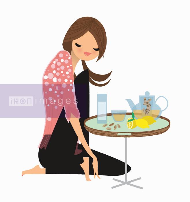 Woman enjoying ginger and lemon tea at small table - Woman enjoying ginger and lemon tea at small table - Nila Aye