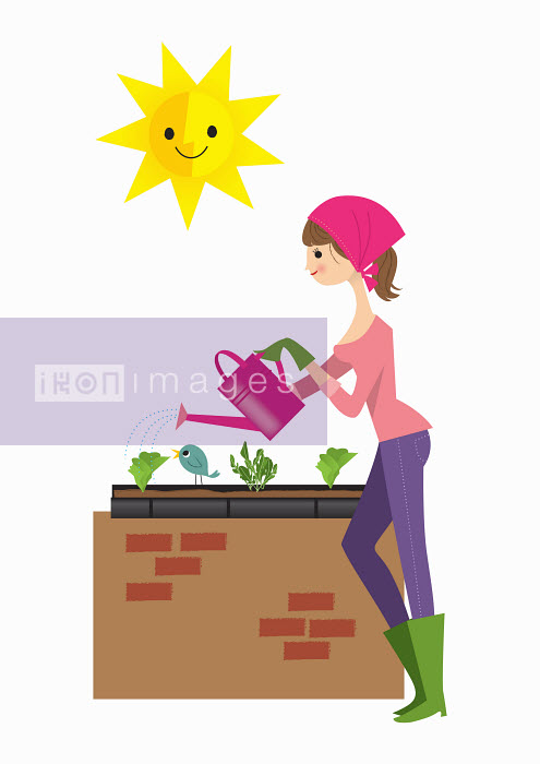 Woman planting lettuce in raised bed - Nila Aye