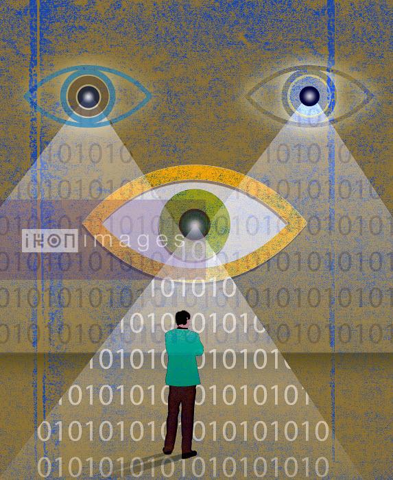 Roy Scott - Man standing in front of large eyes spotlighting binary code