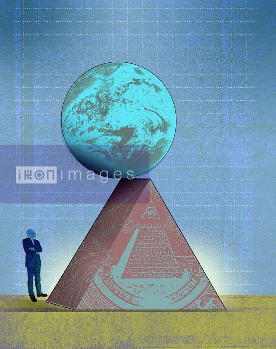 Man looking at globe teetering on edge of United States pyramid - Man looking at globe teetering on edge of United States pyramid - Roy Scott