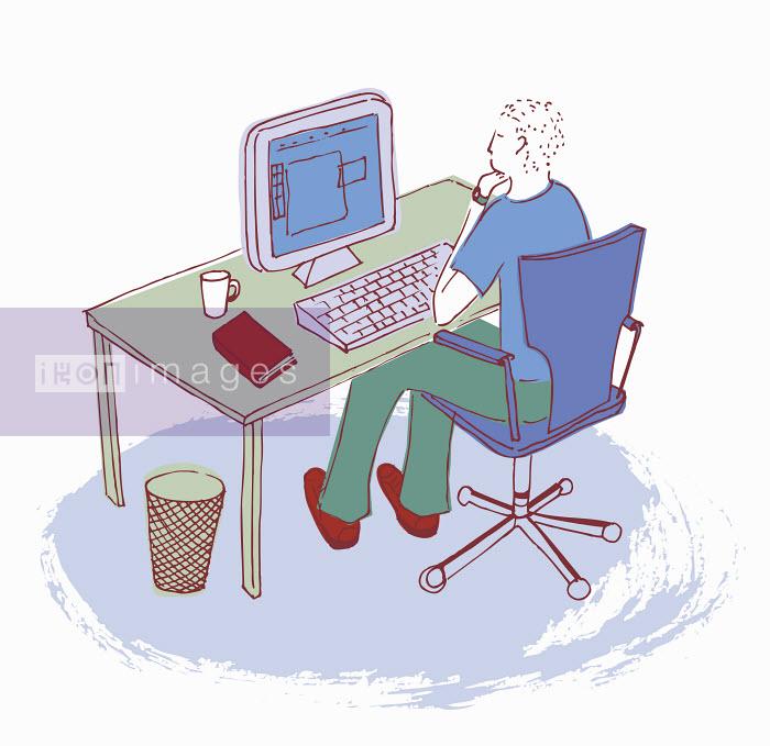 Man working at desk using computer - Man working at desk using computer - Trina Dalziel