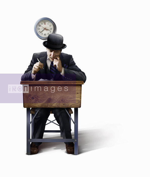 Businessman in bowler hat struggling with exam paper at school desk - Businessman in bowler hat struggling with exam paper at school desk - Derek Bacon