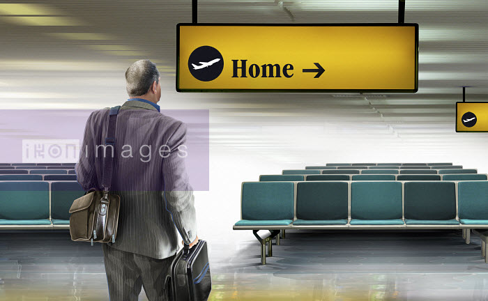 Businessman arriving in airport looking at home direction sign - Businessman arriving in airport looking at home direction sign - Derek Bacon