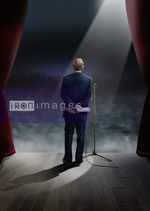 Businessman standing on stage holding microphone behind back - Businessman standing on stage holding microphone behind back - Derek Bacon