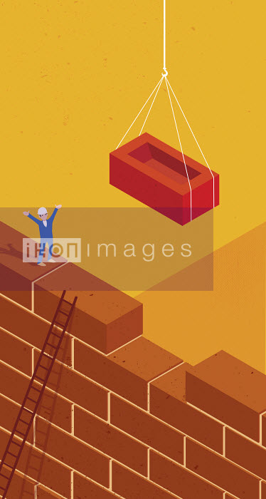 Construction worker guiding large brick into gap in tall wall - Construction worker guiding large brick into gap in tall wall - Nick Diggory