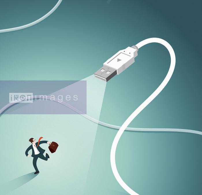 Businessman in spotlight running away from USB plug - Nick Diggory
