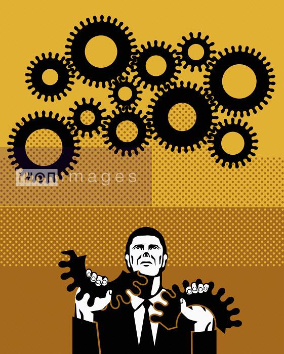 Businessman holding broken cog - Klaus Meinhardt