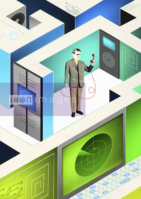 Businessman in technological office cubicle holding disconnected telephone - Businessman in technological office cubicle holding disconnected telephone - Valero Doval