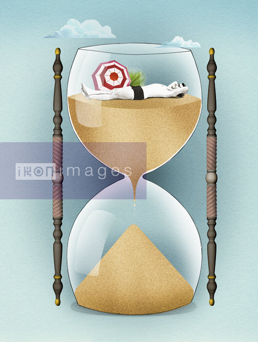 Valero Doval - Man relaxing on sand inside of hourglass