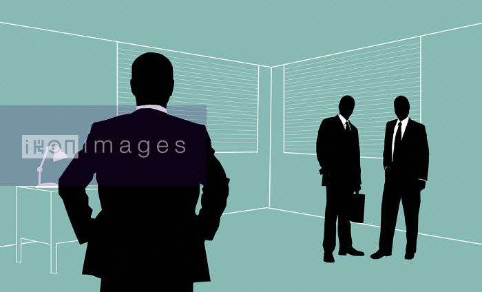 Two businessmen looking at colleague standing isolated - Two businessmen looking at colleague standing isolated - Nick Lowndes