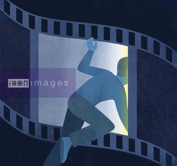Man climbing through film strip - Man climbing through film strip - Mitch Blunt