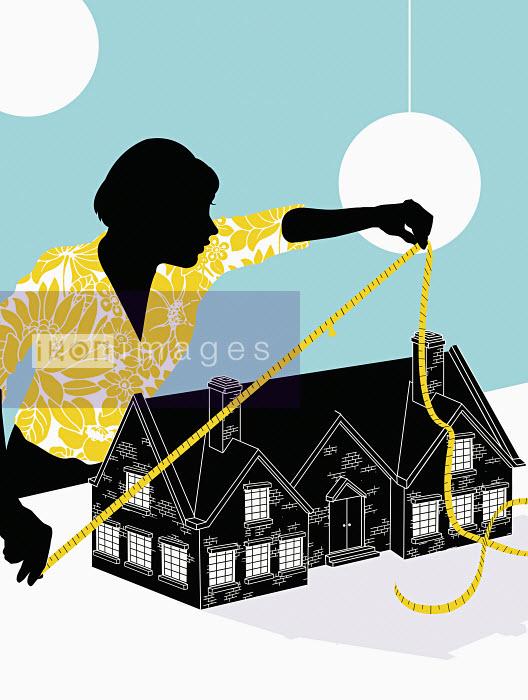 Woman measuring house - Woman measuring house - Neil Webb