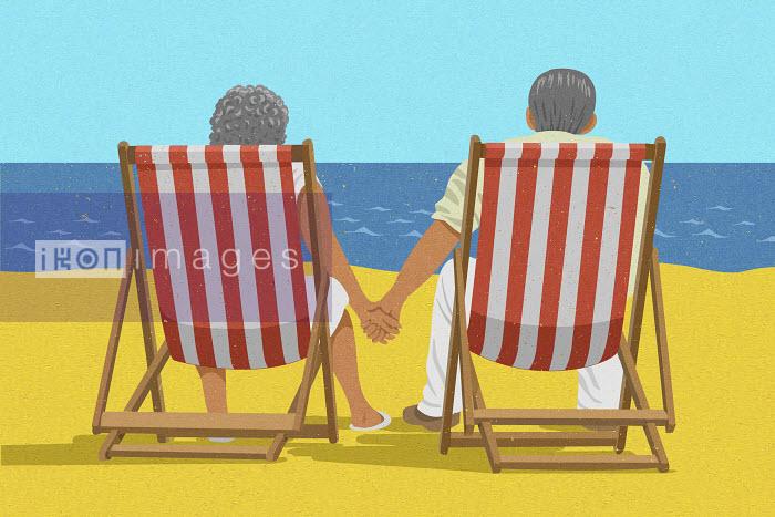 Senior couple sitting hand in hand in deckchairs on beach - John Holcroft
