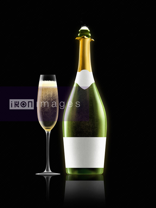 Glass of champagne next to champagne bottle with white label Nick Purser