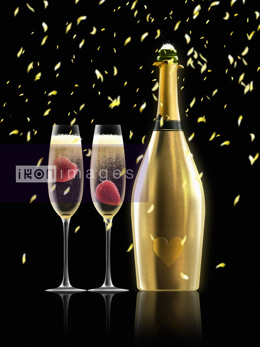 Nick Purser - Confetti falling on two glasses of champagne next to gold champagne bottle