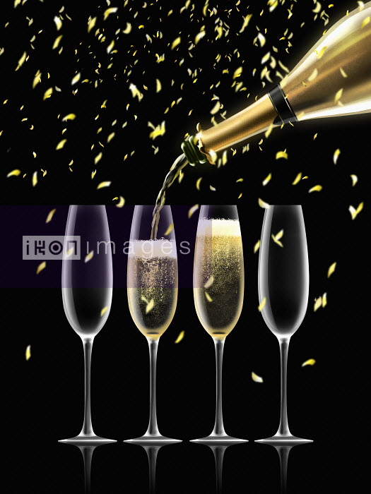 Confetti falling on gold champagne bottle filling four champagne flutes Nick Purser
