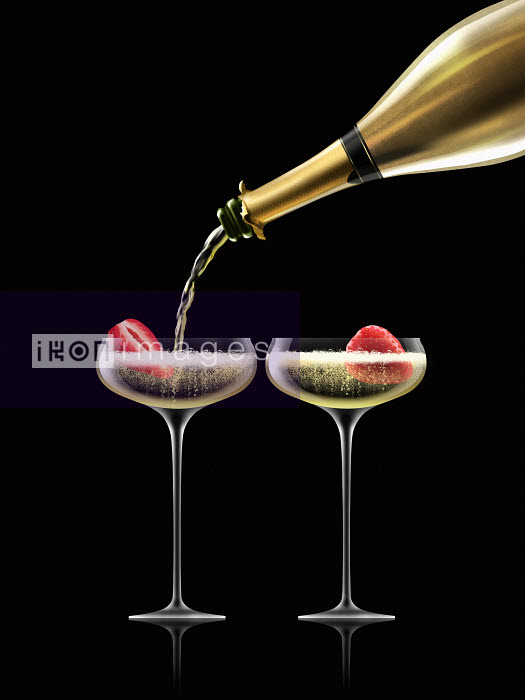 Gold champagne bottle filling coupe glasses containing strawberries - Nick Purser