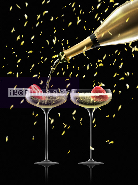 Confetti falling on gold champagne bottle filling two champagne coupes - Nick Purser