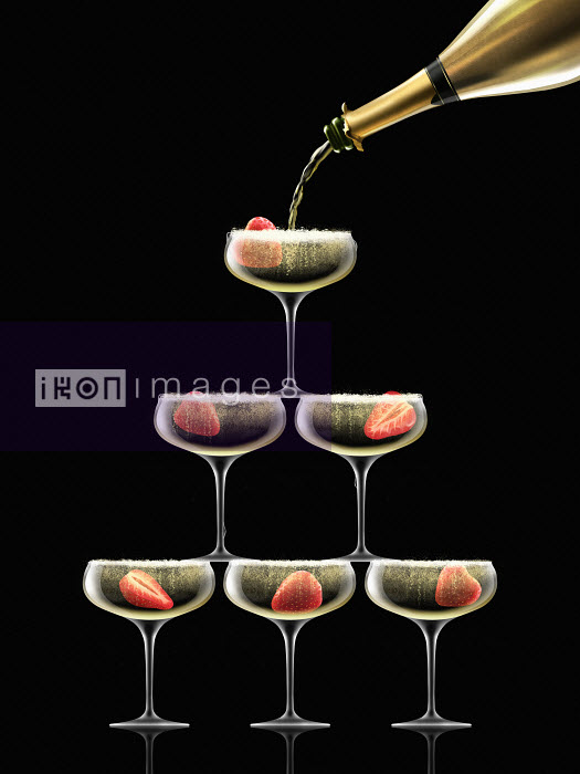 Gold champagne bottle filling coupe glasses in champagne pyramid - Nick Purser