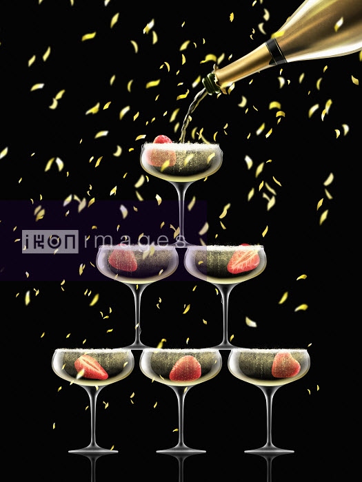 Confetti falling on coupe glasses in champagne pyramid - Nick Purser