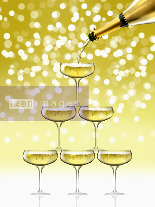 Nick Purser - Champagne bottle filling coupe glasses in sparkling champagne pyramid