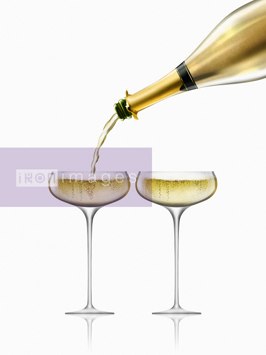 Gold champagne bottle filling two champagne glasses Nick Purser