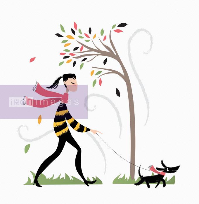 Nila Aye - Woman walking the dog on a windy autumn day