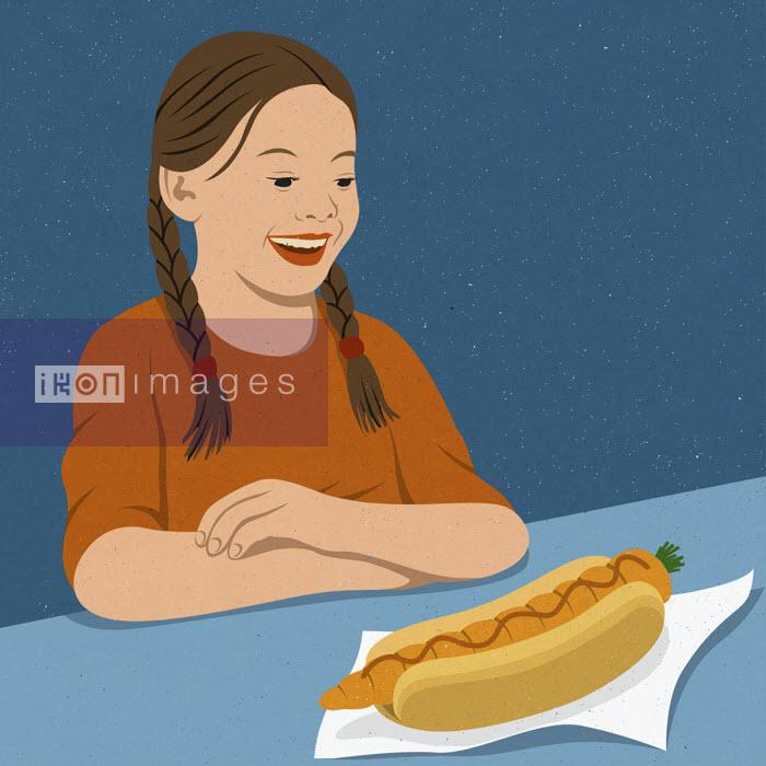 Girl delighted at carrot in hot dog bun John Holcroft