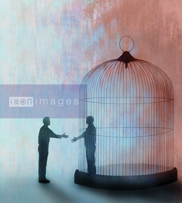 Gary Waters - Man shaking hands with man trapped inside of cage