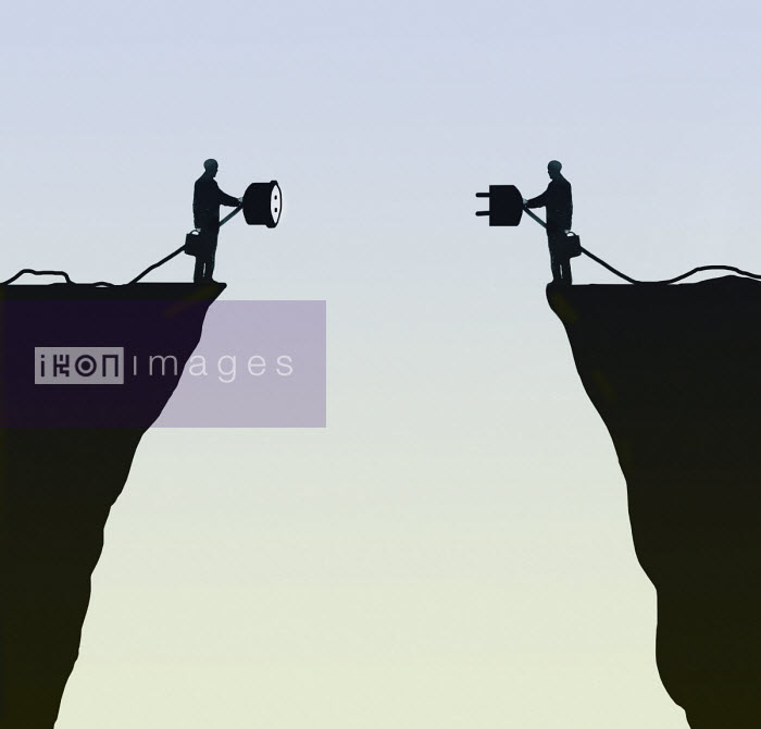 Two businessmen on opposite sides of chasm trying to connect plug and socket Gary Waters
