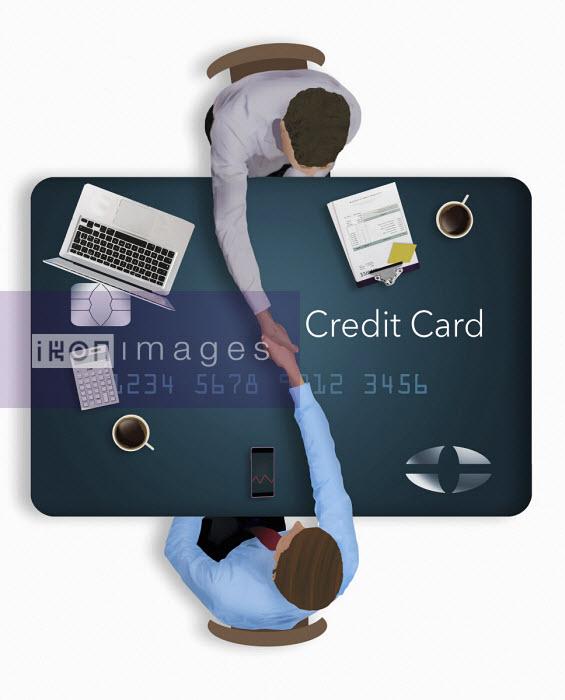 Overhead view of businessmen shaking hands over credit card desk
