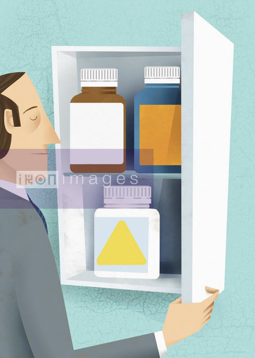 Gregory Baldwin - Tired man choosing pill bottle from medicine cabinet