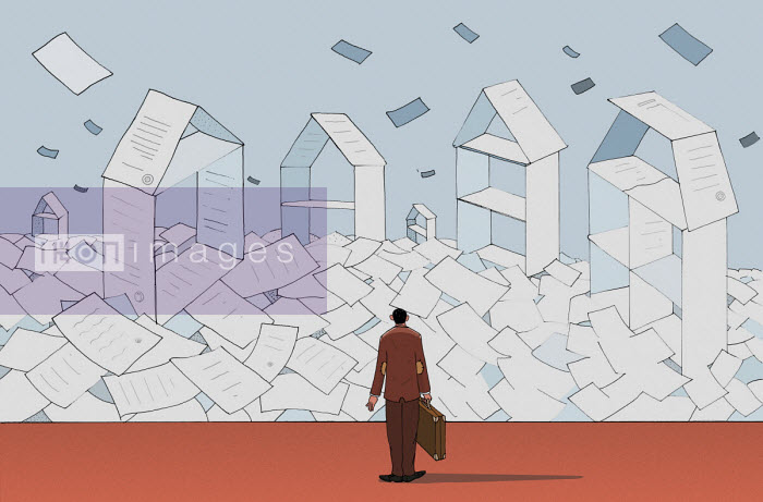 Conveyancing lawyer looking at piles of paper forming houses - Maxim Usik