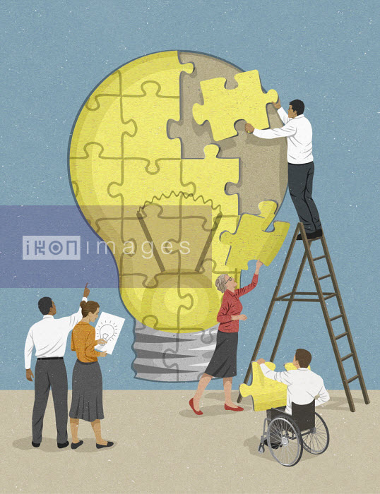 Colleagues working together to complete light bulb jigsaw puzzle - John Holcroft