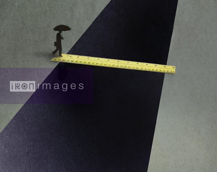 Gary Waters - Businessman walking on ruler to cross gap